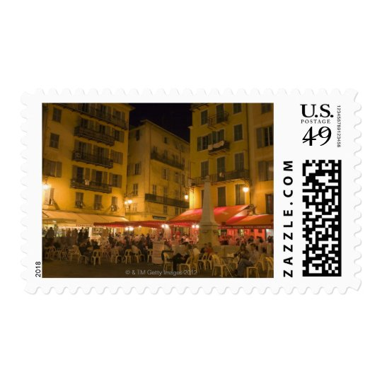 Group of people sitting at a sidewalk cafe, postage