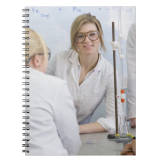 Group of students wearing lab coats and safety 2 notebook