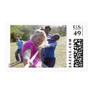Group of teenagers, aged 13,  pulling together postage