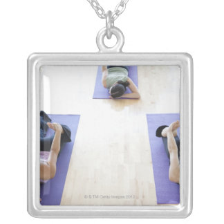 Group of woman stretching on mats in a bright, silver plated necklace