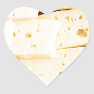 Group slices dry hard yellow cheese on a plate heart sticker
