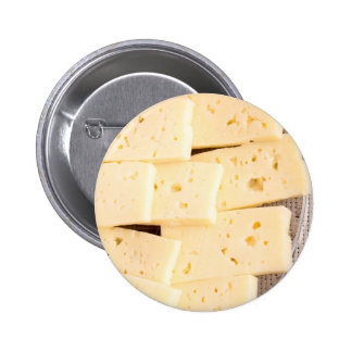 Group slices dry hard yellow cheese on a plate pinback button