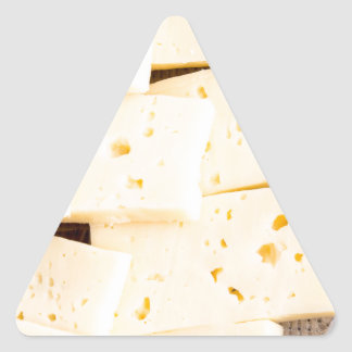 Group slices dry hard yellow cheese on a plate triangle sticker