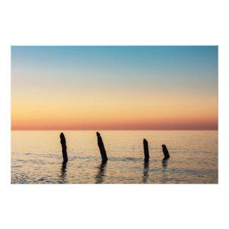 Groynes y puesta del sol en la orilla del mar fotografías