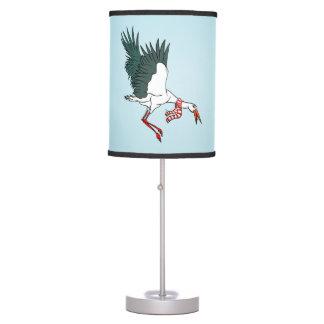 Grúa divertida del dibujo animado que lleva una lámpara de escritorio