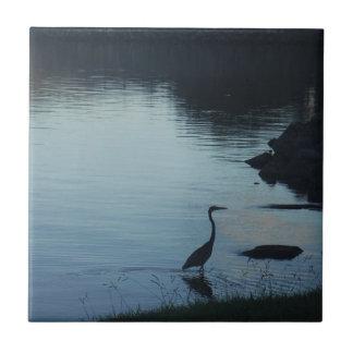 Grúa en el lago en la puesta del sol azulejo cuadrado pequeño