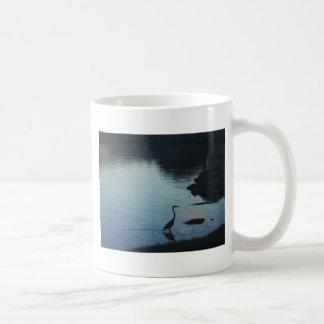 Grúa en el lago en la puesta del sol taza