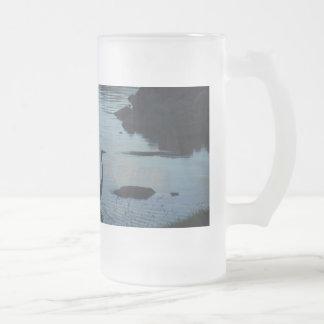 Grúa en el lago en la puesta del sol tazas