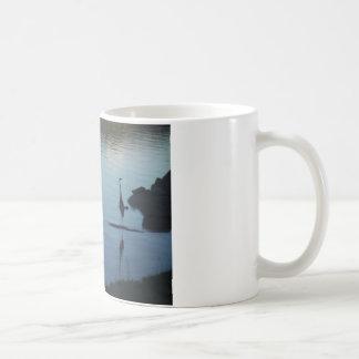 Grúa en el lago en la puesta del sol taza de café