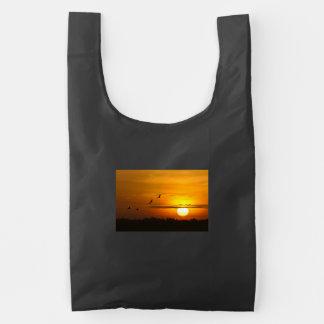 Grúas en la salida del sol bolsa reutilizable