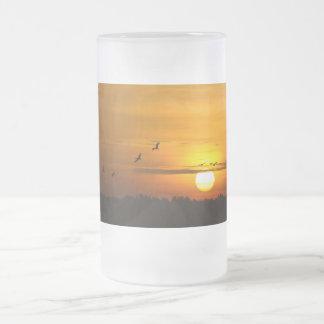Grúas en la salida del sol taza de cristal