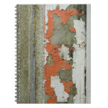 Grunge peeling orange paint on concrete wall spiral note book
