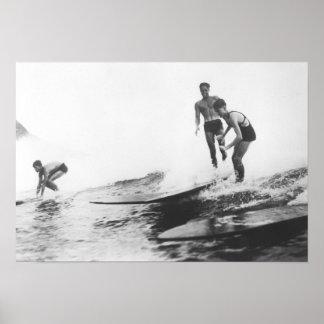 Grupo de personas que practica surf en el practica posters