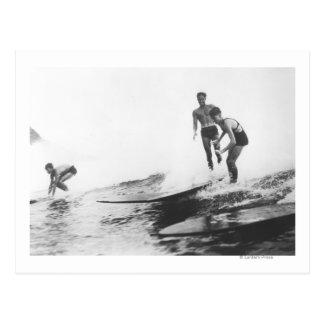 Grupo de personas que practica surf en el postales