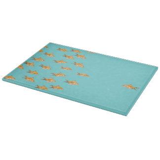 Grupo grande de goldfish que hace frente a un tabla de cortar