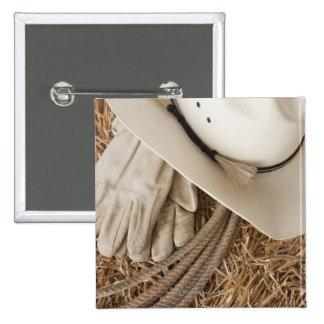 Guantes y cuerda del gorra de vaquero en haystack pin