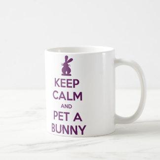 Guarde al mascota tranquilo una taza del conejito