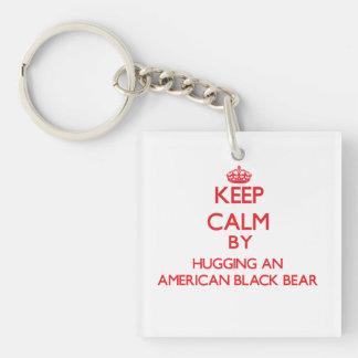 Guarde la calma abrazando un oso negro americano llaveros