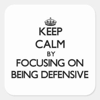 Guarde la calma centrándose en ser defensivo calcomanías cuadradases