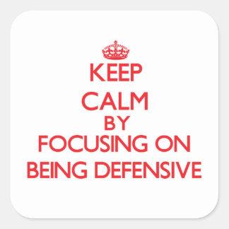 Guarde la calma centrándose en ser defensivo calcomania cuadradas