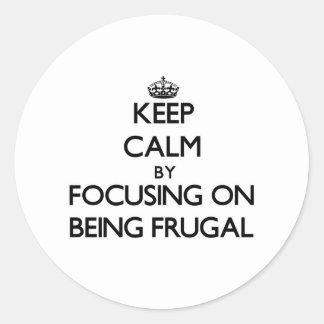 Guarde la calma centrándose en ser frugal etiquetas redondas