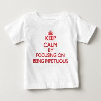 Guarde la calma centrándose en ser impetuoso tee shirts