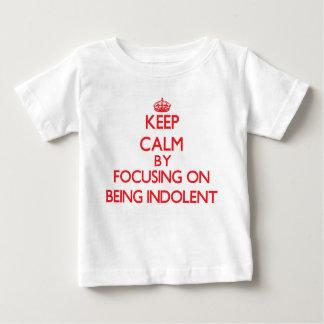 Guarde la calma centrándose en ser indolente tee shirts