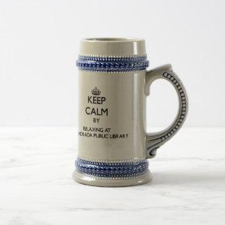 Guarde la calma relajándose en la biblioteca públi taza de café