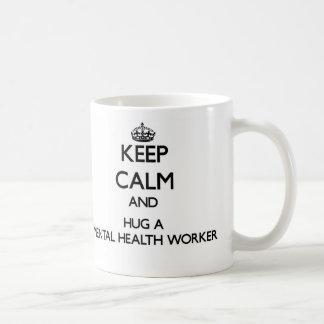 Guarde la calma y abrace a un ayudante de sanidad taza básica blanca