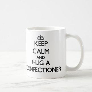 Guarde la calma y abrace a un confitero taza básica blanca