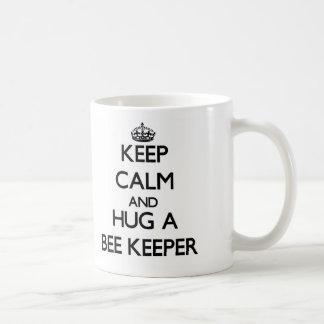 Guarde la calma y abrace a un encargado de la taza básica blanca