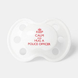 Guarde la calma y abrace a un oficial de policía chupetes de bebé