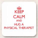 Guarde la calma y abrace a un terapeuta físico posavasos de bebidas