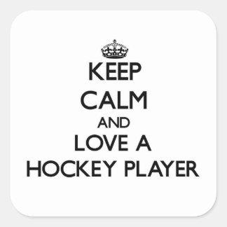 Guarde la calma y ame a un jugador de hockey pegatina cuadrada