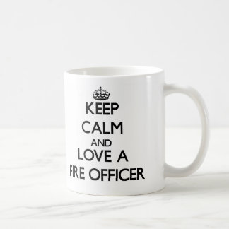 Guarde la calma y ame a un oficial del fuego taza básica blanca