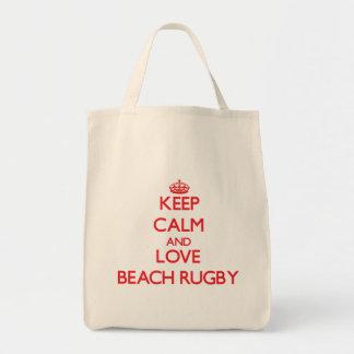 Guarde la calma y ame el rugbi de la playa bolsas de mano