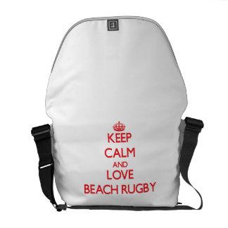 Guarde la calma y ame el rugbi de la playa bolsas de mensajeria