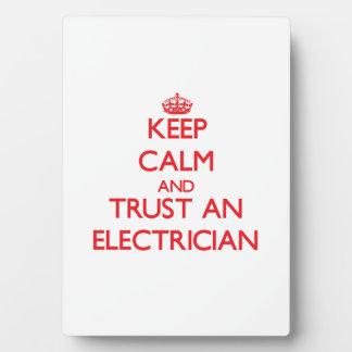 Guarde la calma y confíe en a un electricista placa de madera