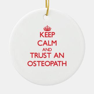 Guarde la calma y confíe en a un osteópata adorno navideño redondo de cerámica