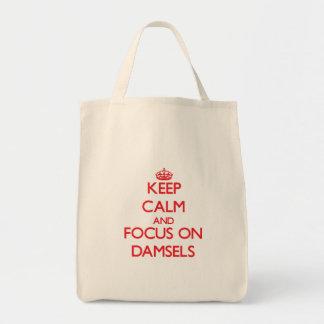 Guarde la calma y el foco en damiselas bolsa lienzo