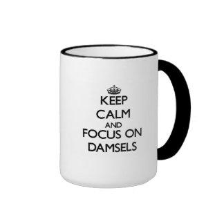 Guarde la calma y el foco en damiselas taza