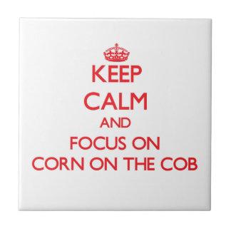 Guarde la calma y el foco en el maíz en la mazorca azulejo