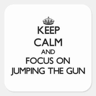 Guarde la calma y el foco en el salto del arma pegatina cuadrada