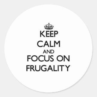 Guarde la calma y el foco en frugalidad etiquetas redondas