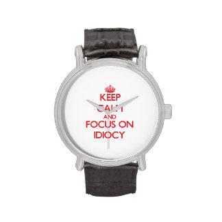 Guarde la calma y el foco en idiotez reloj de mano