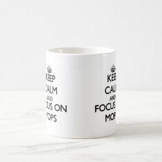 Guarde la calma y el foco en las fregonas taza básica blanca