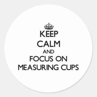 Guarde la calma y el foco en las tazas de medición etiqueta redonda