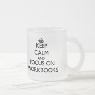 Guarde la calma y el foco en los libros de trabajo tazas de café