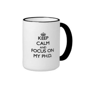 Guarde la calma y el foco en mi Ph D Tazas