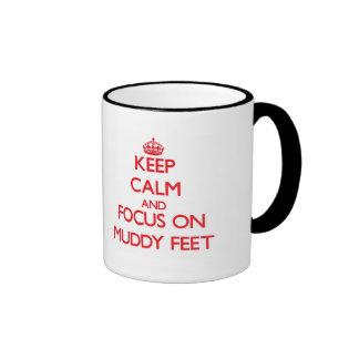 Guarde la calma y el foco en pies fangosos taza de café